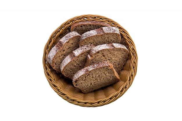 白で隔離されるバスケットで茶色のパンのトップビュー