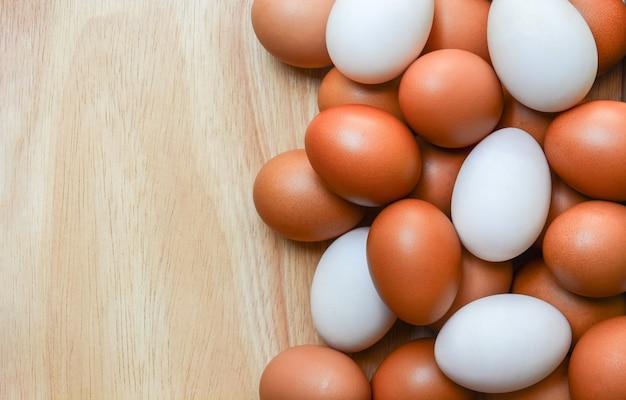 Вид сверху коричневых куриных яиц и белых утиных яиц на деревянном фоне