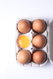 Вид сверху коричневых яиц на коробке для яиц, изолированных на белом фоне.