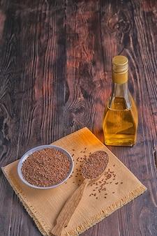 Вид сверху коричневых семян льна и льняного масла в бутылке