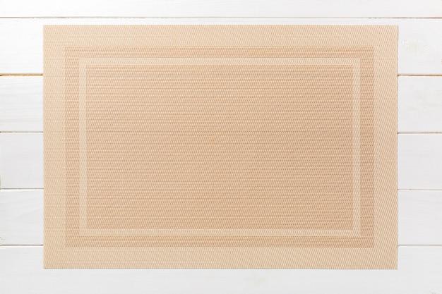 皿の茶色のランチョンマットの平面図。あなたのデザインのための空のスペースで木製の背景
