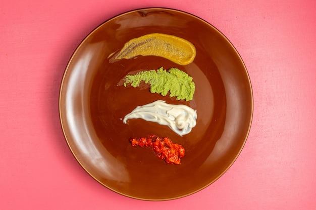 Вид сверху коричневой круглой тарелки с разными соусами на розовой стене