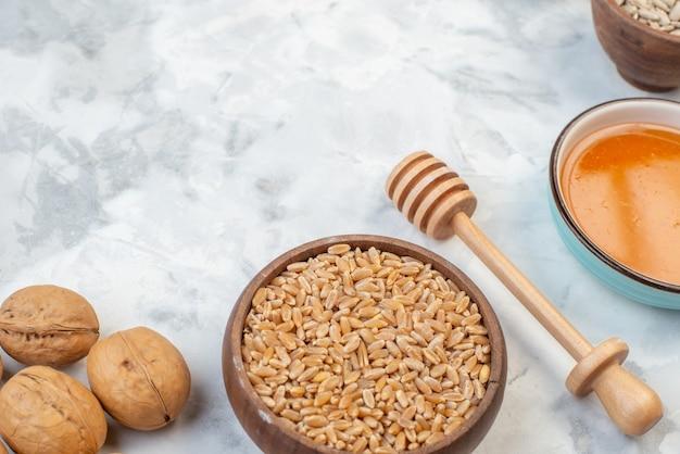 Вид сверху коричневого риса в небольшой миске мед деревянной ложкой грецких орехов на фоне льда со свободным пространством