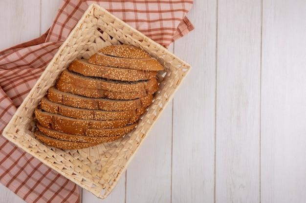 Вид сверху коричневого нарезанного початка с семенами в корзине на клетчатой ткани на деревянном фоне с копией пространства