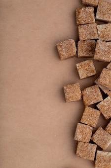 Взгляд сверху кубов желтого сахарного песка аранжировало на предпосылке текстуры коричневой бумаги с космосом экземпляра