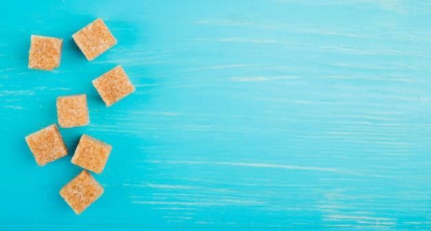 Взгляд сверху кубов желтого сахарного песка разбросанных на голубую деревянную предпосылку с космосом экземпляра