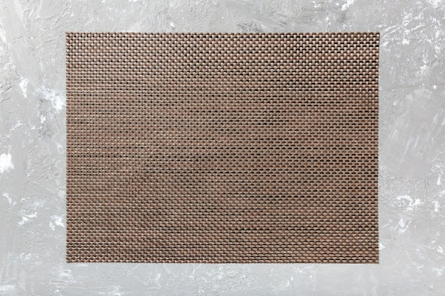 セメントの背景に茶色のテーブルナプキンの平面図です。空きスペースのあるマット