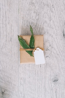 Top view of brown wrapped gift box with tag and green leaves on wooden table