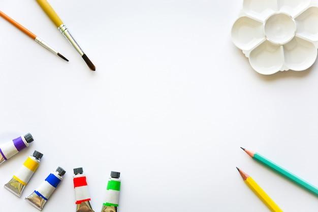 Вид сверху кистей, цветных трубок, карандашей и палитры на белом фоне для рисования