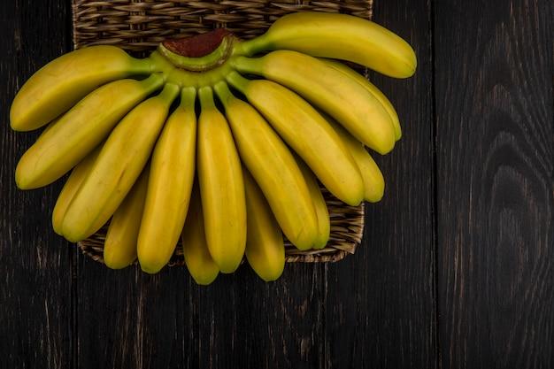 Вид сверху гроздь бананов в плетеной корзине на темном