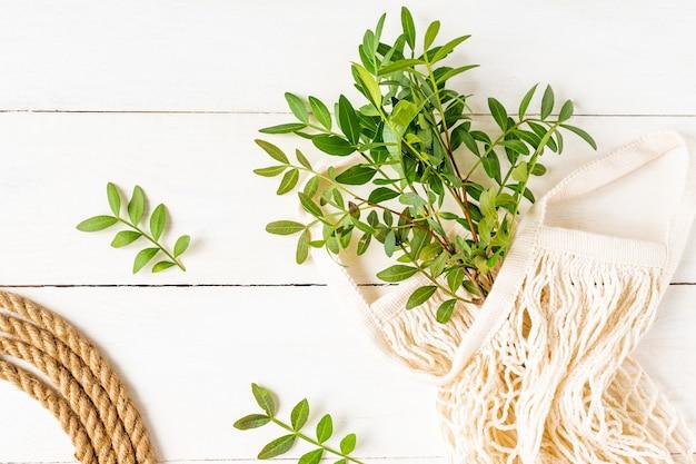 綿のメッシュバッグとジュートロープの緑の枝の束の上面図。環境にやさしい背景。
