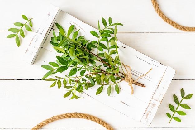 木製トレイとジュートロープ上の緑の枝の束の上面図。環境にやさしい背景。
