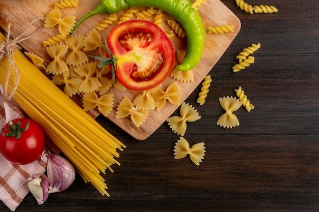 Вид сверху на пучки сырых макарон с чесноком и макарон с помидорами и острым перцем на доске на деревянной поверхности