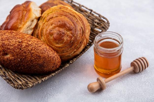 ガラスの瓶に蜂蜜と白い背景の上の木製の蜂蜜スプーンとバケツのパンの上面図