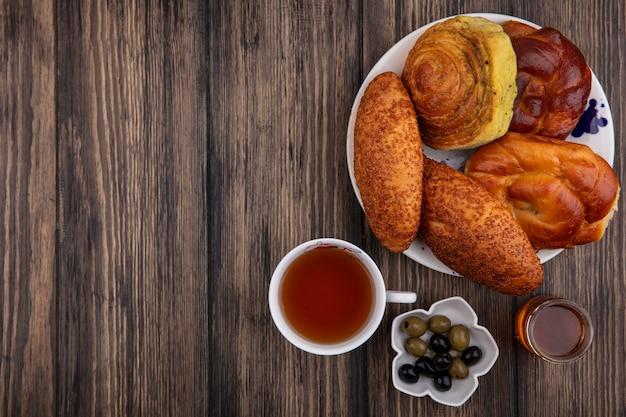 ボウルにオリーブとコピースペースと木製の背景に蜂蜜とお茶のカップとプレート上のパンの上面図