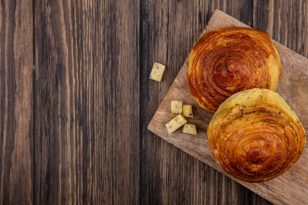 コピースペースのある木製の背景にチーズのスライスを刻んだ木製のキッチンボード上のパンの上面図