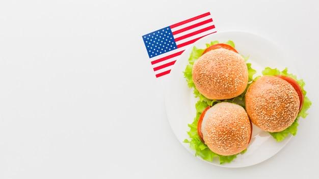 Взгляд сверху бургеров на плите с космосом экземпляра и американским флагом