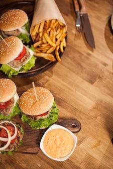 木製のテーブルにレタスとハンバーガーの平面図です。シェフナイフ。