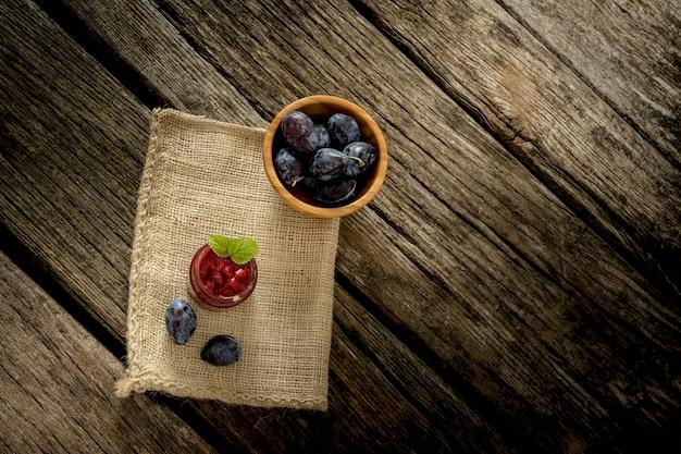 Вид сверху мешковины из мешковины, лежащей над деревенским текстурированным деревянным столом со стеклянной банкой, полной варенья, спелых слив и миской сочных слив на нем.