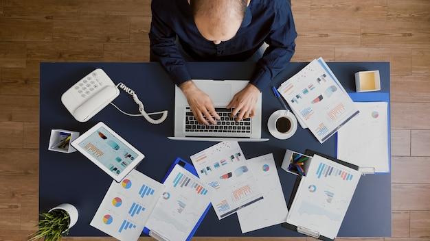Вид сверху на бизнес-директора, сидящего за столом в офисе стартап-компании, анализирующего корпоративные финансы ...