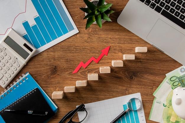 Вид сверху на бизнес-предметы и стрелку роста с деревянными блоками