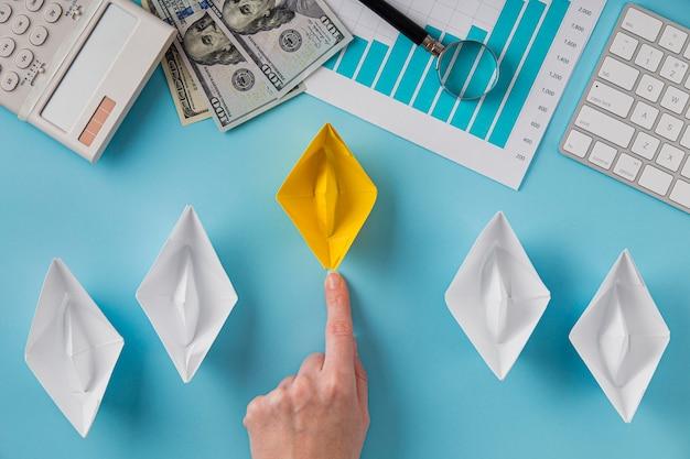 Вид сверху на бизнес-предметы с диаграммой роста и рукой, указывающей на цветной бумажный кораблик