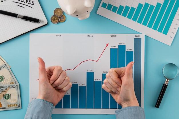 Вид сверху на бизнес-элементы с диаграммой роста и руками, поднимающими пальцы вверх