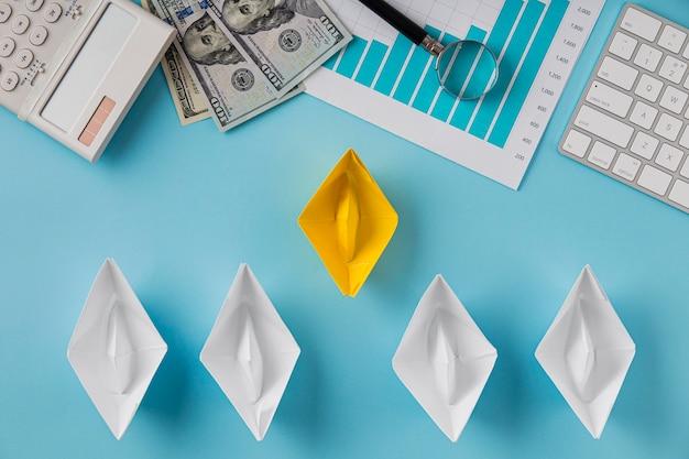 Вид сверху бизнес-предметов с диаграммой роста и бумажными корабликами