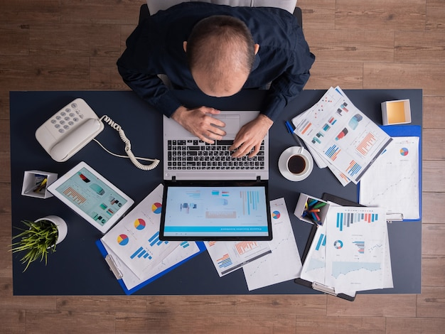 机に座って、ラップトップで入力し、財務統計とビジネス戦略に取り組んでいる企業のオフィスのビジネスマンの上面図。ドキュメントをスクロールするtouchepadを使用する起業家。