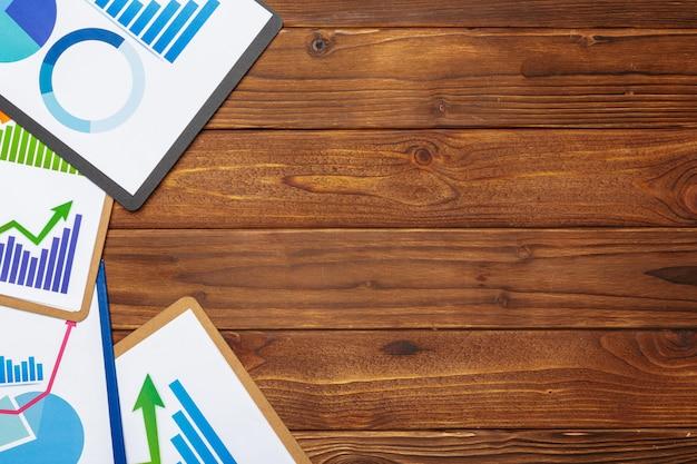 나무 테이블에 비즈니스 종이 차트 또는 그래프의 상위 뷰