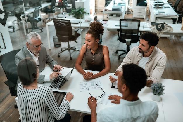 現代のオフィスで一緒に働いている間何かを議論しているビジネスマンの上面図