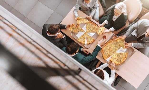 仕事の場所で一緒にピザを食べてフォーマルな服装のビジネス人々の平面図です。仕事での成功は、前向きな態度を取ることから始まります。