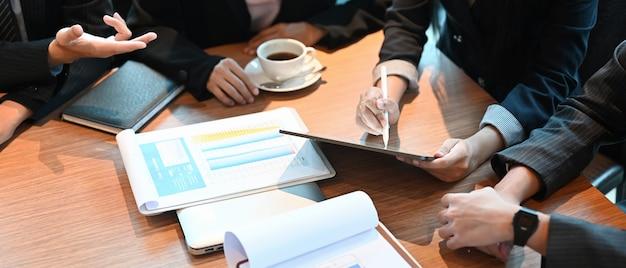 Вид сверху деловых людей работает с планшетным компьютером и оформляет документы за деревянным рабочим столом.