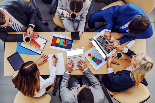 Вид сверху деловых людей, сидящих в зале заседаний и работающих над важным проектом для крупного клиента.