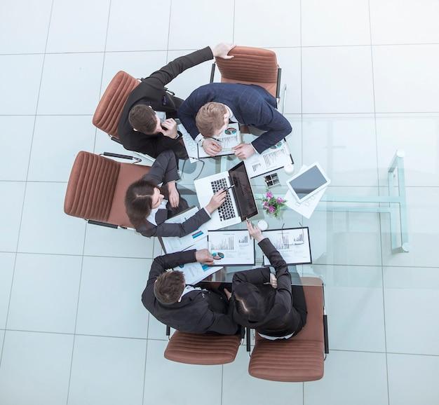 현대 직장에 대한 회사의 재무 계획을 논의하는 비즈니스 팀의 상위 뷰.사진에는 텍스트를 위한 빈 공간이 있습니다.