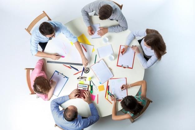 白い背景の上の丸いテーブルに座って、事業チームの平面図です。チームワークの成功のコンセプト