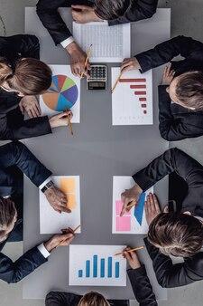 机の後ろに座って、レポートを確認し、話しているビジネスチームの上面図
