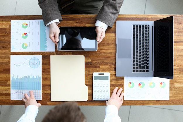 パートナーと新しいプロジェクトを議論するビジネスマンの平面図です。画面上のコピースペースでタブレットを使用する労働者。ラップトップ、テーブルに統計データがあるドキュメント。ビジネス会議と交渉のコンセプト