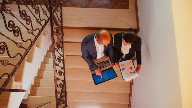 ビジネスビルの階段でオフィスの同僚と話しているラップトップを保持しているビジネスマンの上面図。現代の金融職場で働くプロの成功したビジネスマンのグループ。