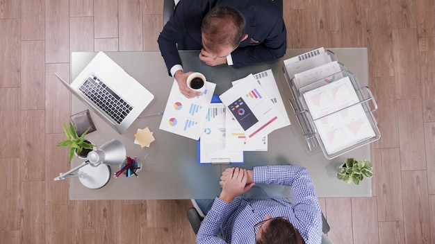 협업 회의 중 커피를 마시는 정장을 입은 사업가의 상위 뷰