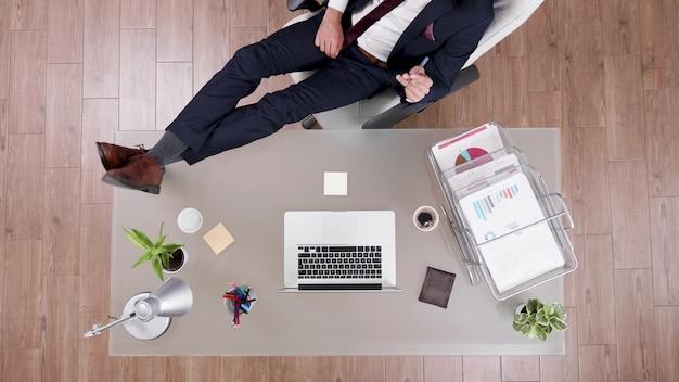 ノートパソコンの財務グラフを分析するオフィスの机の上に足でリラックスしたままスーツを着たビジネスマンの上面図。経営投資でスタートアップ企業のオフィスで働くエグゼクティブマネージャー