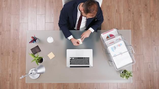 会社の文書を分析した後、財務戦略で働いている付箋にアイデアを書きながら電話で話しているスーツを着たビジネスマンの上面図。投資会議を計画している起業家の男