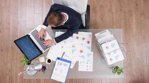 スタートアップオフィスの経営投資プロジェクトで働いている間、ラップトップコンピューターで会社の戦略を入力するビジネスマンの上面図。管理統計を分析するスーツのマネージャー
