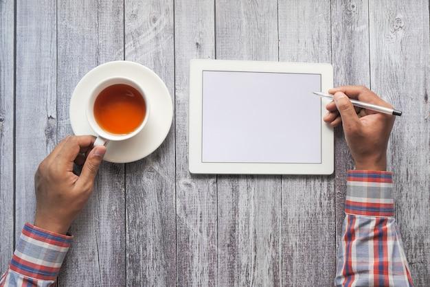 사무실 책상에 디지털 태블릿을 사용하는 사업가의 상위 뷰