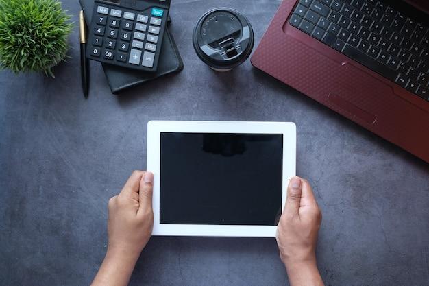 사무실 책상에서 디지털 태블릿을 사용하는 사업가의 상위 뷰