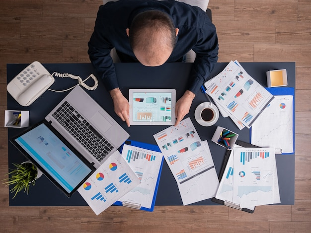 財務チャートを分析するタブレットpcを使用してビジネスマンの上面図