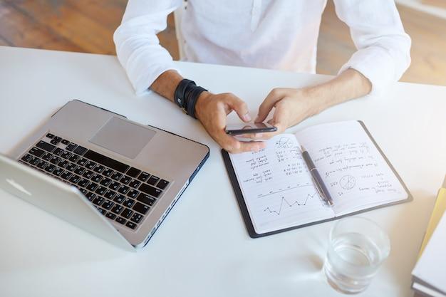 사업가의 상위 뷰는 사무실에서 흰 셔츠를 입는다.