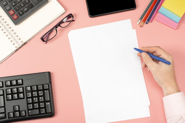 Вид сверху бизнесмена, работающего с финансовой отчетностью. современный розовый офисный стол с блокнотом, карандашом и множеством вещей.