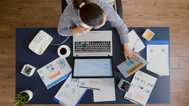 회사 통계를 설명하는 관리자와 논의하는 여성 사업가의 상위 뷰