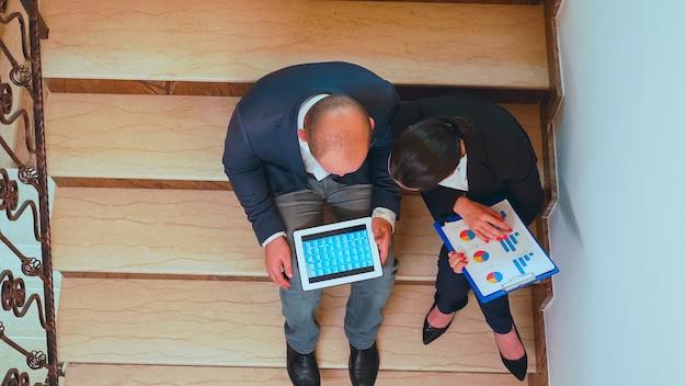 レポートを分析するビジネスビルの階段で会社のマネージャーと話しているクリップボードを保持している実業家の上面図。現代の金融職場で働くプロのビジネスマンのグループ。